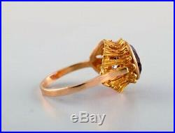 Swedish goldsmith. 18 carat gold ring adorned with purple semi precious stone